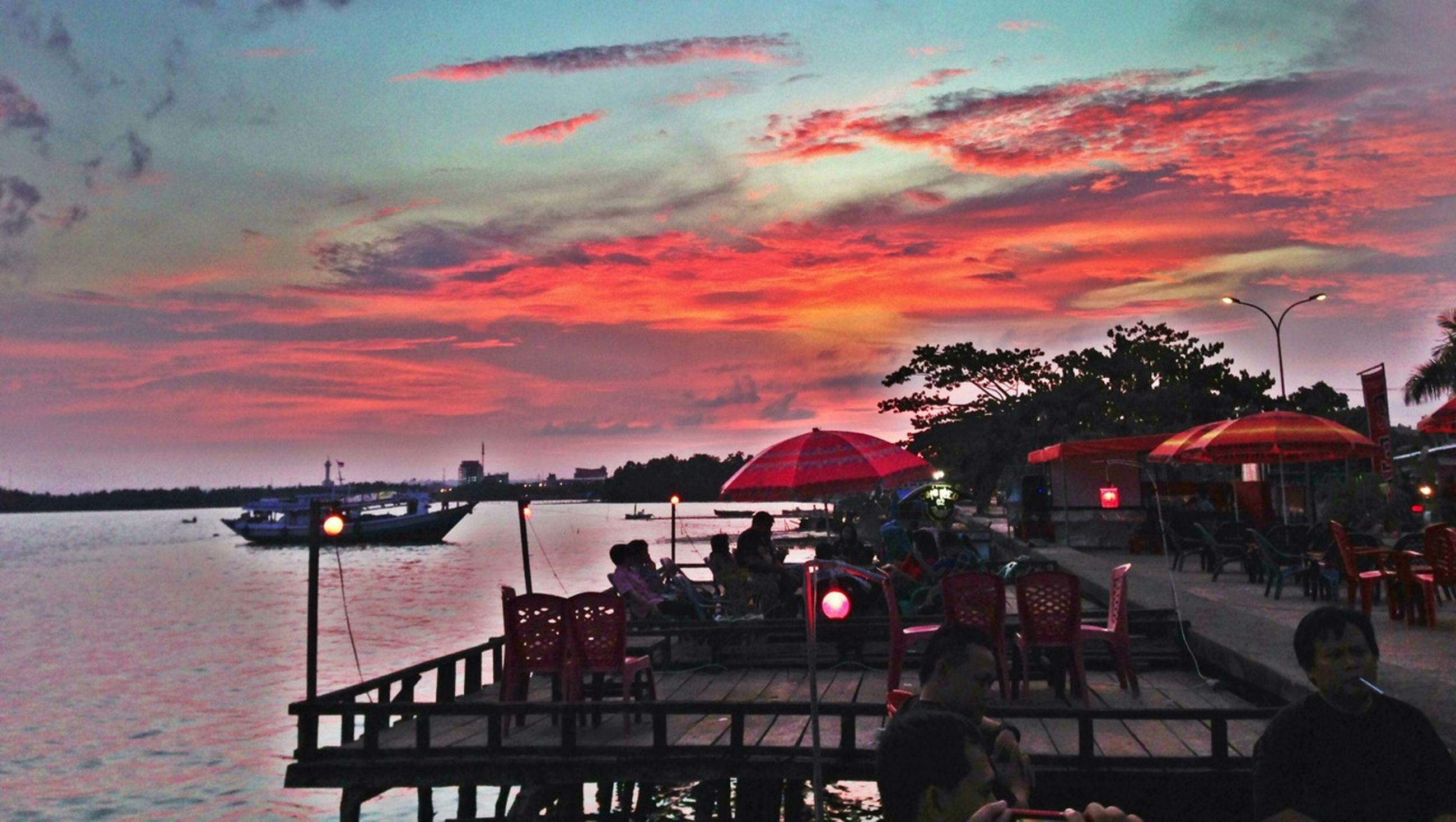 sunset, sky, water, cloud - sky, sea, transportation, lifestyles, dusk, leisure activity, person, mode of transport, silhouette, nautical vessel, nature, men, cloud, orange color, railing, outdoors
