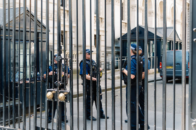 Police officers guarding 10 Downing Street entrance gate in the City of Westminster. 10 of Downing Street is the residence of the Prime Minister of the United Kingdom 10 Downing Street Brexit Britain London Officer Theresa May Uk Architecture Attraction British Capital City Conservative Control Crisis Downing Downing Street Election England English European  Famous Fence Gate Government House KINGDOM Landmark Leader Minister Parliament Police Political Politician Politics Power Prime Prime Minister Protection Residence Safety Security Street Terror Terrorism Travel Westminster Whitehall Teamwork