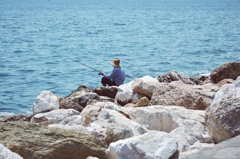 Side view of man fishing while sitting on rock at sea