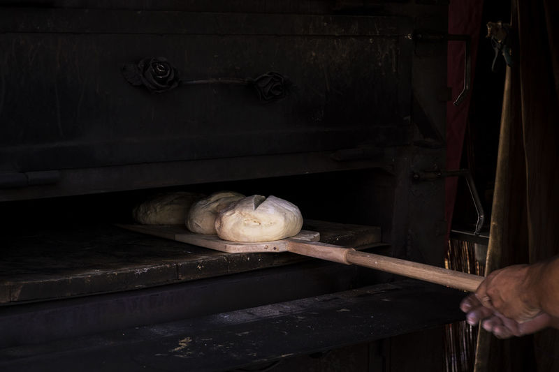 Man putting bread dough in the wood oven