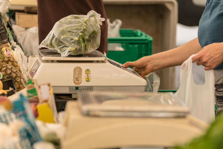 Midsection of woman weighing vegetable in supermarket