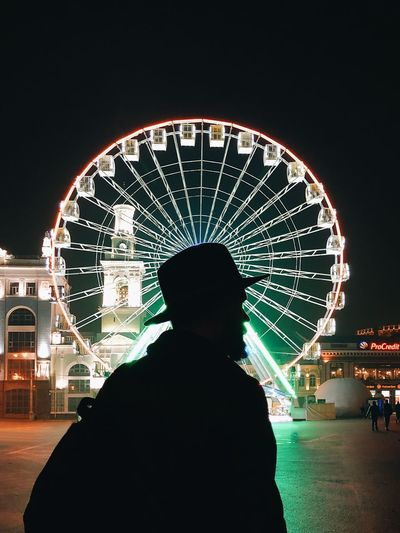 Rear view of silhouette people against illuminated ferris wheel at night