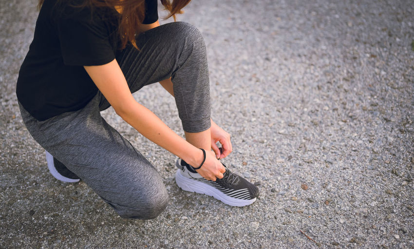 Young women knee sitting and wrapping a shoelace , workout , inspiration and motivation concept