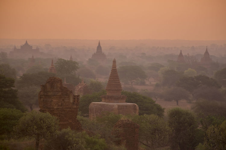 Stupas against orange sky during sunset