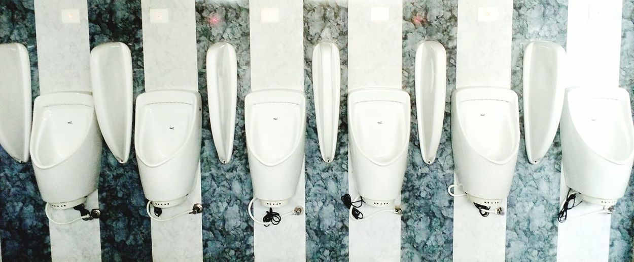 Panoramic view of white ceramic urinals on wall at public restroom