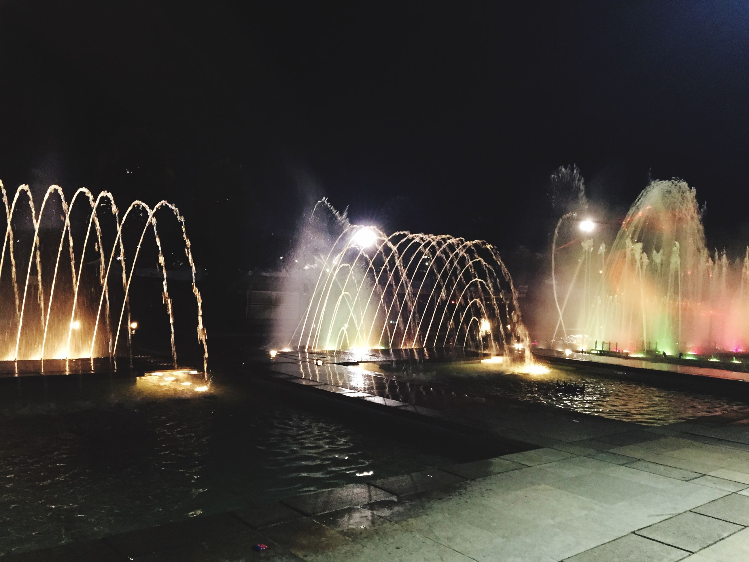 night, illuminated, fountain, long exposure, motion, water, spraying, built structure, city, architecture, blurred motion, building exterior, glowing, light trail, splashing, light - natural phenomenon, sky, incidental people, outdoors, clear sky