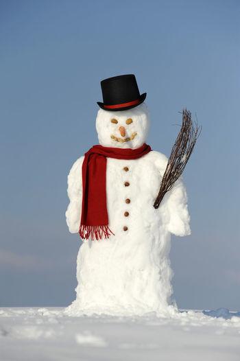 Snowman on field against blue sky