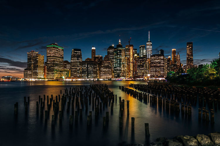 Illuminated modern buildings by river at manhattan in city during night
