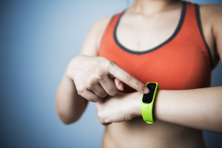 Midsection Of Woman Wearing Fitness Tracker At Home
