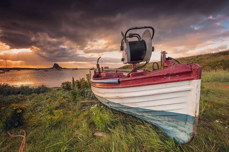 Boat Moored On Grassy Shore Against Cloudy Sky During Sunset