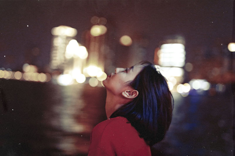 Side View Of Thoughtful Woman Standing Against Illuminated City At Night