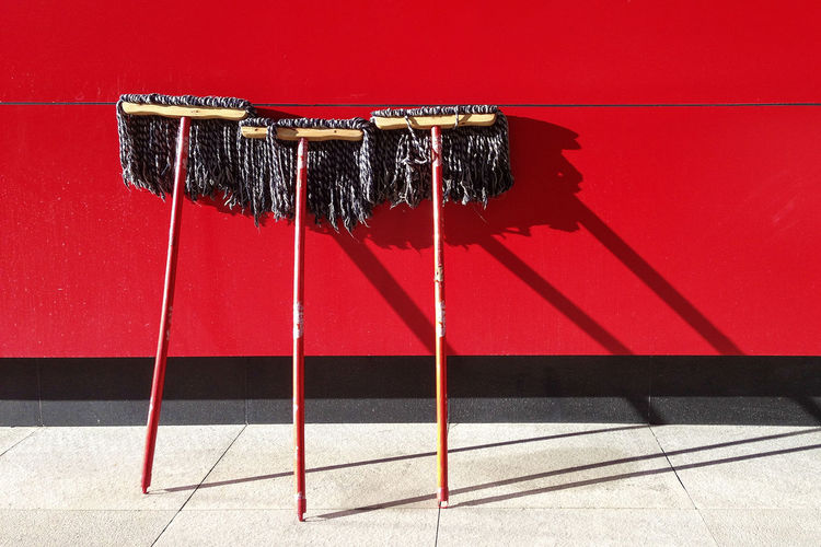 Brooms on red wall
