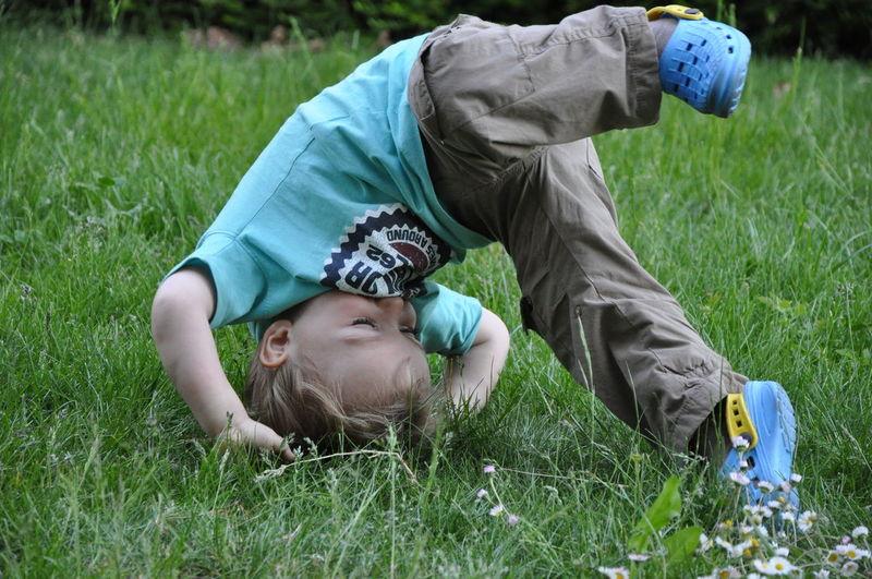 Playful little boy doing headstand on grass