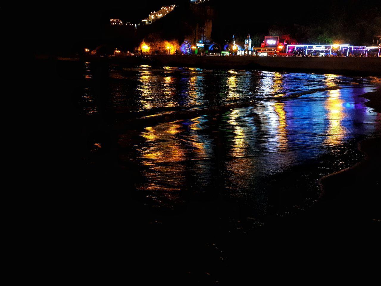 RIVER BY ILLUMINATED CITY AT NIGHT