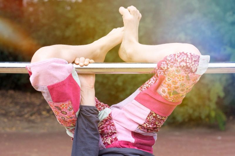 Low Section Of Girl Exercising On Gymnastics Bar