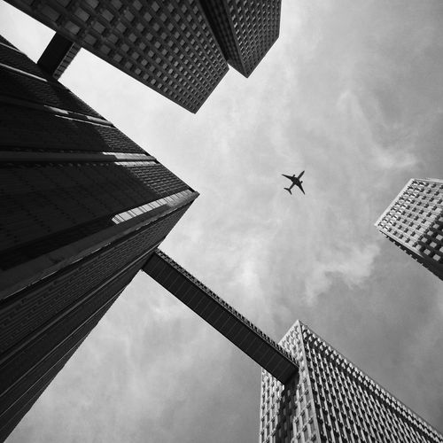 Low angle view of buildings against airplane