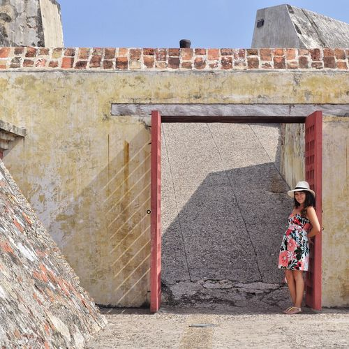 Young Woman Standing Amidst Doorway Of Historical Building