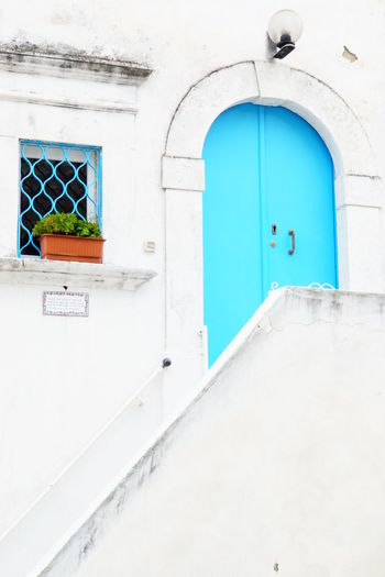 Blue And White Colour Blue Door And Window Building Exterior Contrasting Colours Lamp Over Doorframe Lines And Shapes No People Outdoors Plant In Front Of Window Semicircular Doorframe Stone Walls Whitewashed