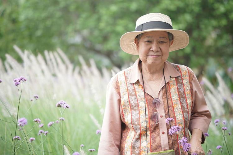 Portrait of woman wearing hat standing against plants