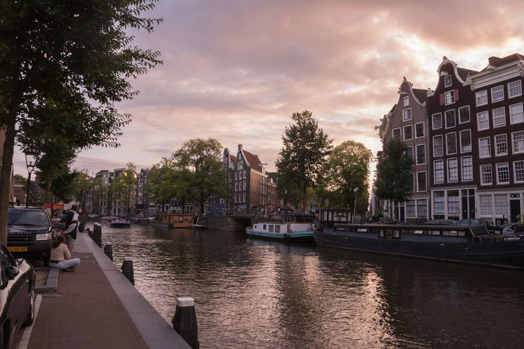 Canal in city against cloudy sky during sunset