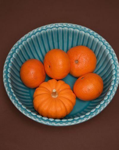 a pumpkin in a nest of mandarins Citrus Fruit Food Freshness Fruit Healthy Eating Mandarins Nest No People Plate Pumpkin Strange