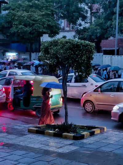 Woman with cars on street in city