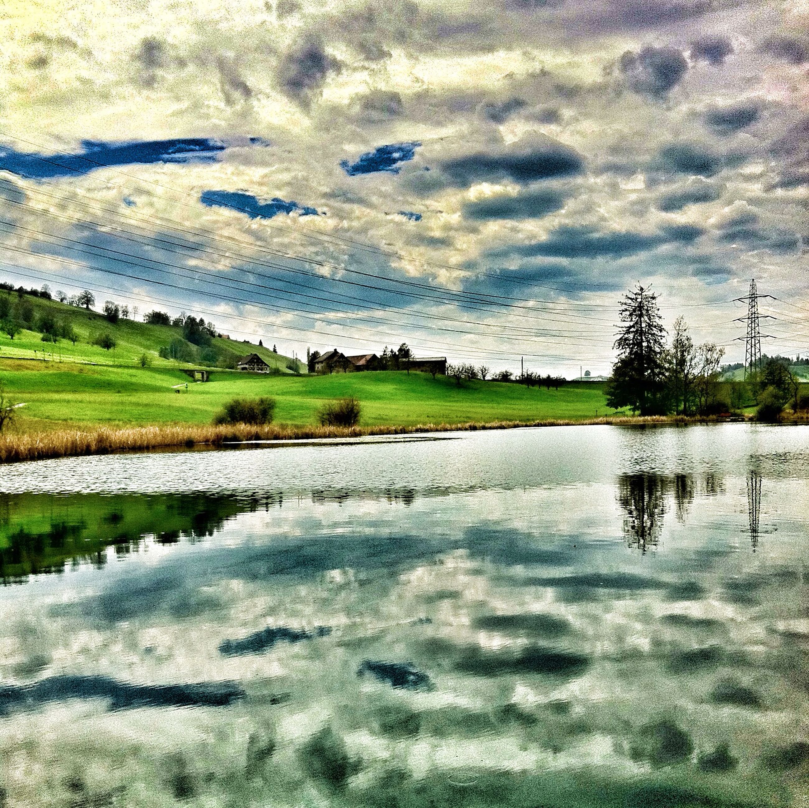 tranquil scene, tranquility, water, sky, scenics, landscape, cloud - sky, beauty in nature, nature, lake, grass, field, reflection, cloudy, tree, cloud, idyllic, river, outdoors, non-urban scene