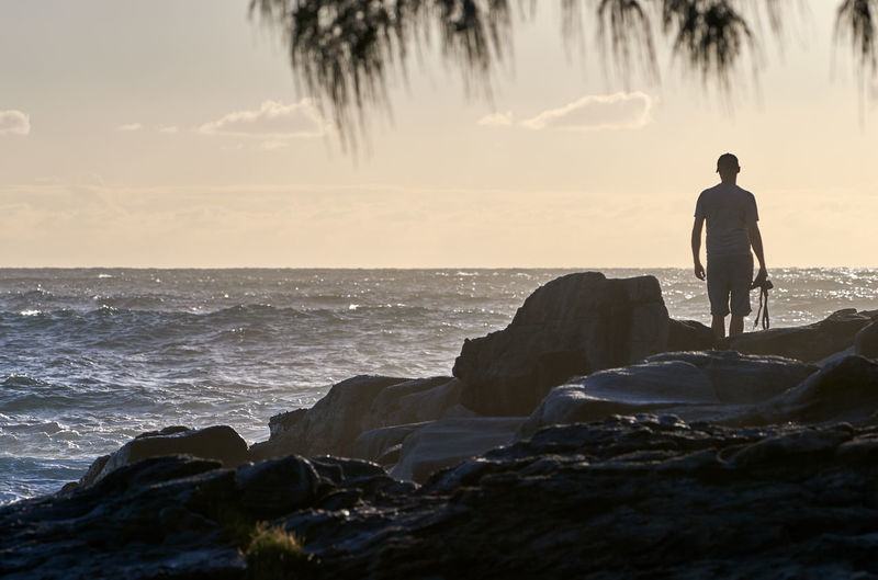 Rear view of silhouette man looking at sea while standing on rock against sky during sunset