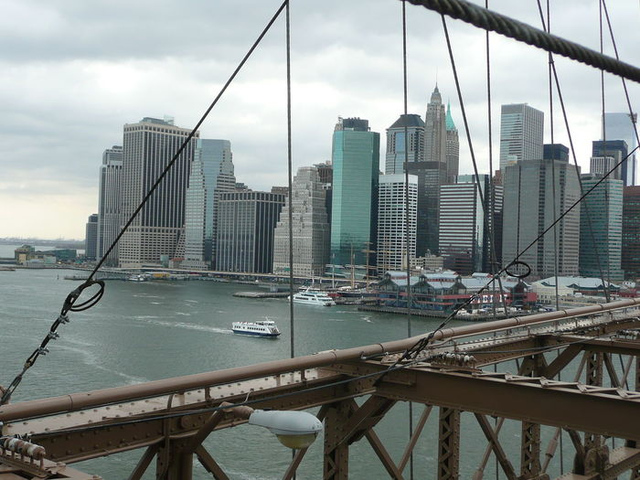 Skyscrapers By East River Seen Through Manhattan Bridge Against Cloudy Sky
