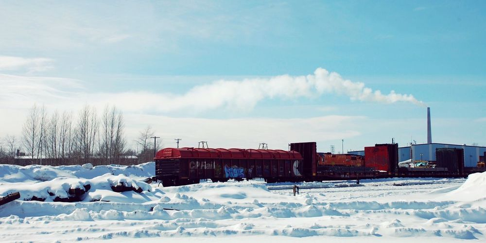 Freight train by snow covered field against cloudy sky