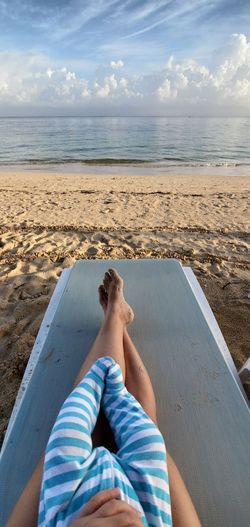 Top view of mother and baby legs on a beach chair by the water