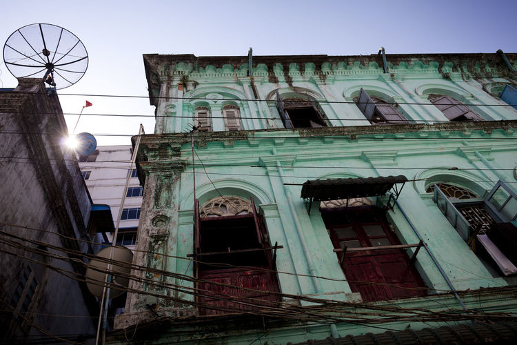 An colourful house front in the old town of Yangon, Myanmar. Architecture Architecture Building Exterior Built Structure City Colourful Damaged Façade Green Historic Building History House House Front Low Angle View No People Old Buildings Outdoors Sunset Window Yangon