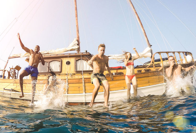 Frontal view of young millennial friends jumping from sailboat on sea ocean trip - Rich guys and girls having fun together in summer boat party day - Exclusive vacation concept on warm bright filter Luxury Friends Summer Young People Millenials Millennials Vacation Travel Fun Happy Sailing Boat Party Trip Sailboat Yacht Moment Ibiza Sail Caribbean Jump Jumping Island Hopping Water