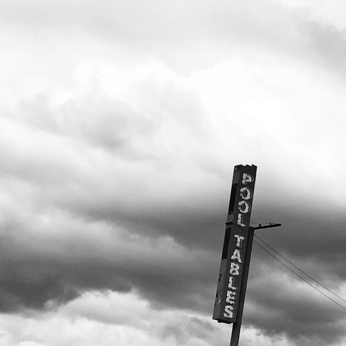 Ross Farrell Photography Blackandwhite Black Text Western Script Communication Guidance Low Angle View Sky Direction Cloud - Sky Day No People Outdoors Road Sign Architecture