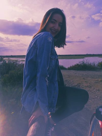 Side view of young woman sitting on railing against sky during sunset