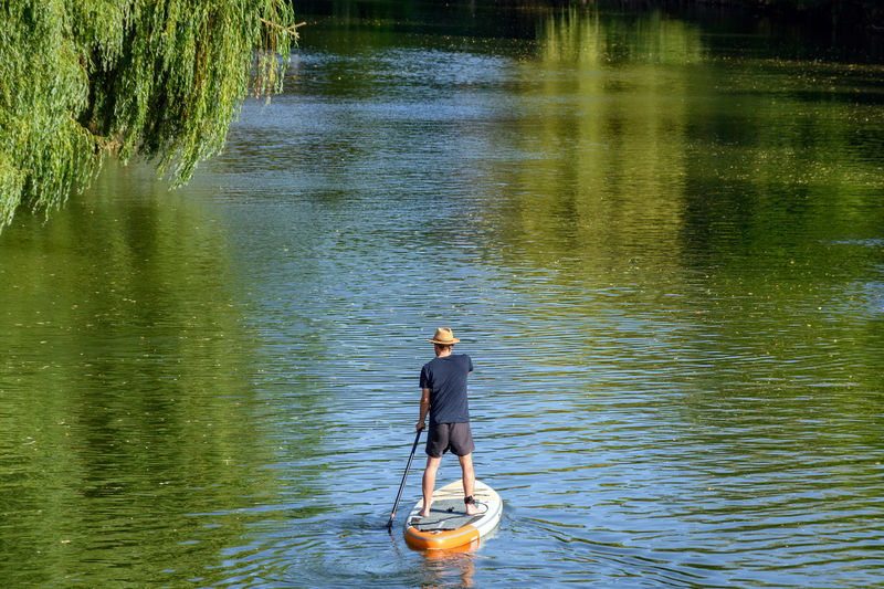 Rear view of man standing in lake