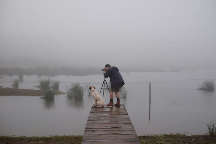 Misty morning missions in the Misty Hills of Nyanga, Zimbabwe. Africa Beauty In Nature Cold Dam Jetty Lifestyles Man And Dog Mist Misty Morning Nature Nature Pet Photographer Pier Scenics Tranquil Scene Tranquility Water Young Adult Young Men