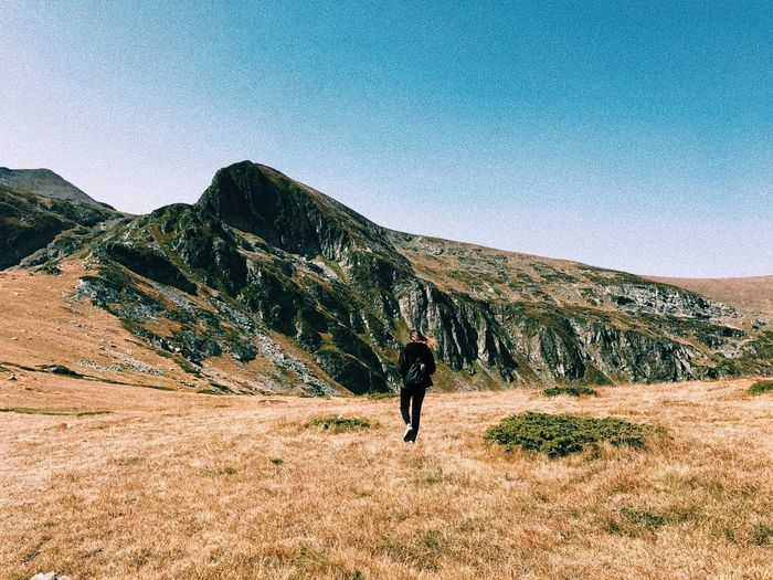 Rear view of man walking on mountain against clear sky
