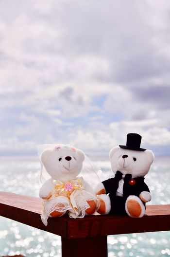 Teddy bears on railing over sea against cloudy sky