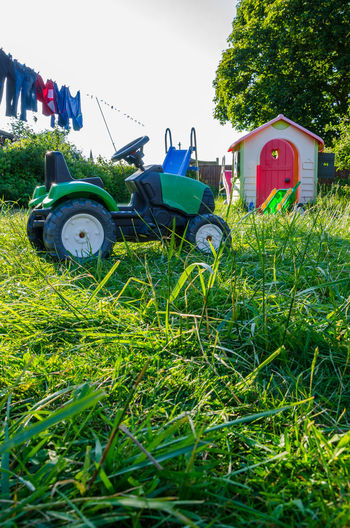 Long grass and garden toys in a back garden. Agricultural Machinery Agriculture Architecture Back Garden Day Field Garden Grass Green Color Growth Laundry Line Nature No People Outdoors Play Hard Residential Garden Rural Scene Sky Toy Tractor Tractor Transportation Tree Washing Line