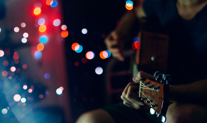Midsection of man playing guitar by defocused lights