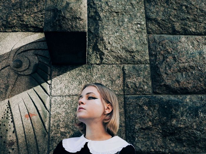 Portrait of a girl looking away against wall