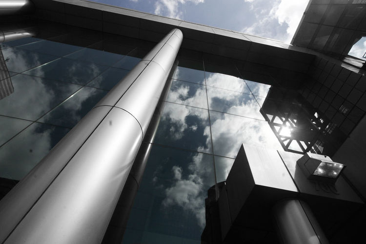Low angle view of modern building against sky on sunny day
