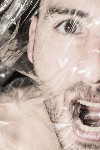 Close-up portrait of man wrapped in plastic