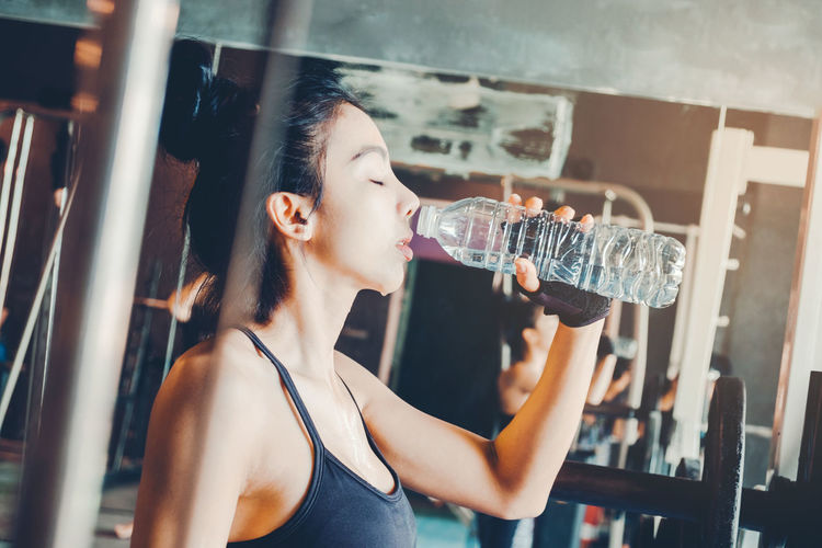 Side view of young woman holding water bottle in gym