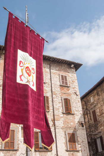Gubbio, Perugia, Italy Architecture Belief Building Building Exterior Built Structure Cloud - Sky Communication Day Flag Hanging Low Angle View Nature No People Outdoors Place Of Worship Red Religion Sky Spirituality Window