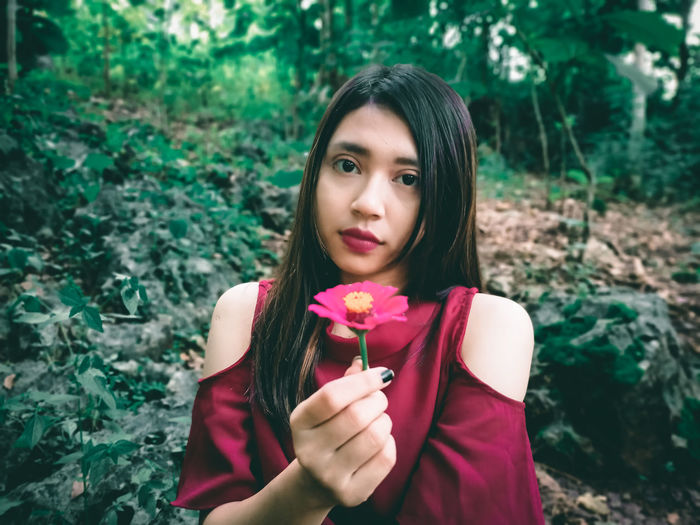 Portrait of beautiful woman holding red flower