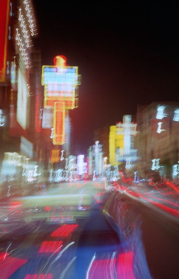 Digital composite image of illuminated city street and buildings at night