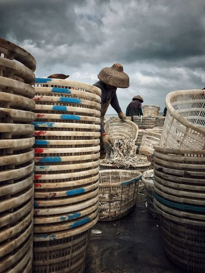 Workers Emptying Fish From Baskets