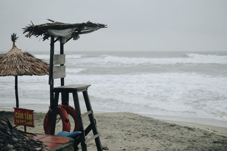 Lifeguard chair by thatched roof at beach against sky